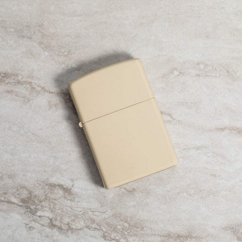 Lifestyle image of Classic Flat Sand Windproof Lighter laying on a marble surface