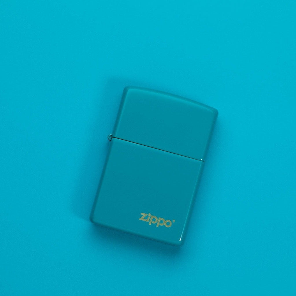 Lifestyle image of Classic Flat Turquoise Zippo Logo Windproof Lighter laying on a turquoise surface