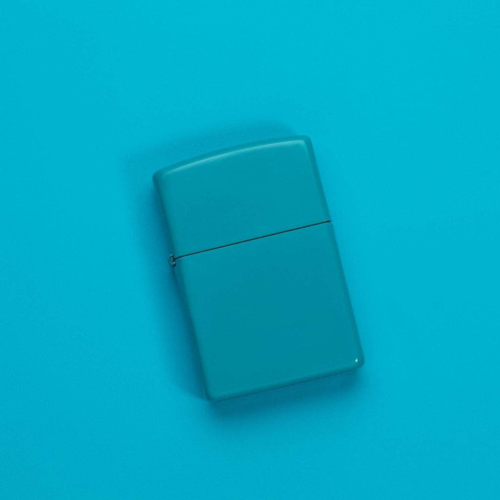 Lifestyle image of Classic Flat Turquoise Windproof Lighter laying on a turquoise surface