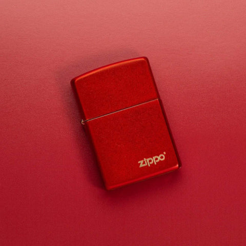 Lifestyle image of Classic Metallic Red Matte Zippo Logo Windproof Lighter laying on a red surface