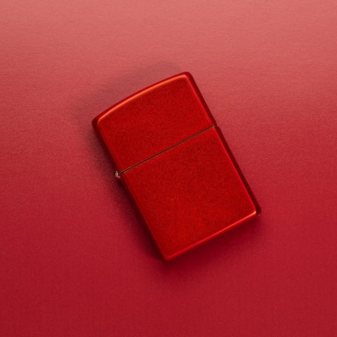 Lifestyle image of Metallic Red Windproof Lighter laying on a red surface