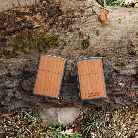 Lifestyle image of WOODCHUCK USA Cherry Emblem Windproof Lighter, laying on a log with one lighter showing the front and the other showing the back