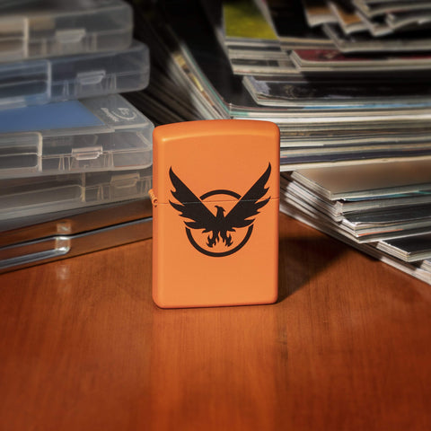 Tom Clancy's The Division 2 orange matte lighter, front view of lighter standing on a wooden desk with video game cases and magazines