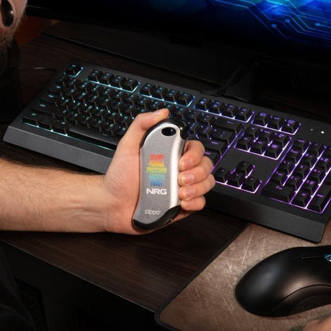 Silver NRG Chicago Huntsman Team: HeatBank® 9s Rechargeable Hand Warmer in hand with a mouse and keyboard in the background