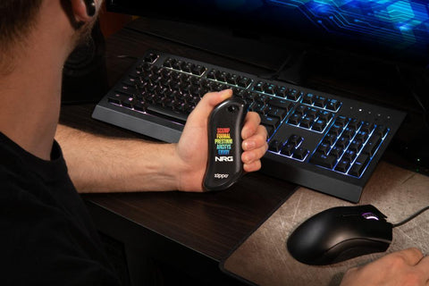 Black NRG Chicago Huntsman Team: HeatBank® 9s Rechargeable Hand Warmer in hand, with a mouse and keyboard in the background