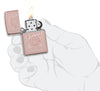 Reimagine Zippo High Polish Rose Gold Windproof Lighter lit in hand