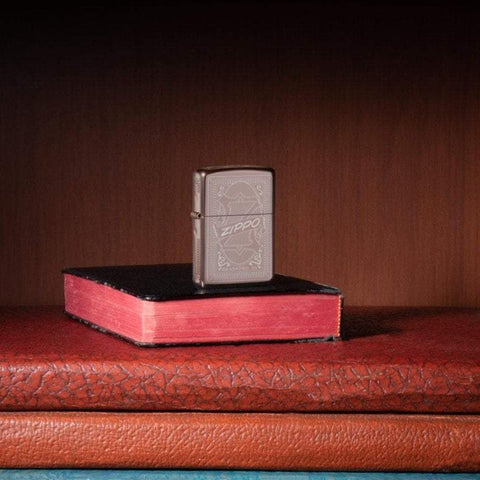 Lifestyle image of Reimagine Zippo High Polish Rose Gold Windproof Lighter, standing in a book case on books