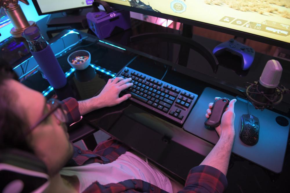 Lifestyle image of Black Heatbank 9s Gaming hand warmer in hand with a mouse and keyboard