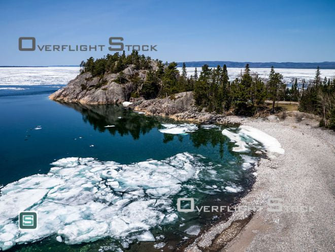 Stock aerial photo. It is early May and there is still ice covering sheltered portions of Lake Superior. This is near the mouth of the Montreal River. Click To View Location