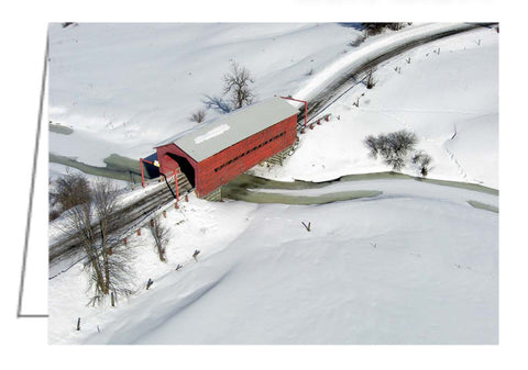 A photo greeting card of a red covered bridge in winter.