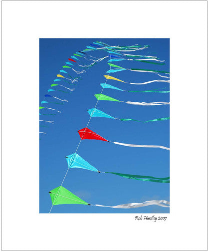 Matted Print - A string of kites against a blue sky.