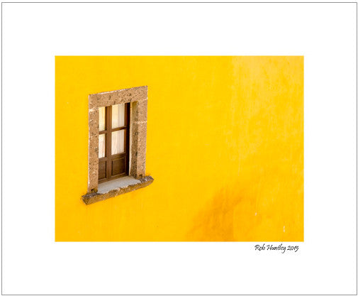 Window on a yellow wall. A window opens to the street on a yellow stucco wall in San Miguel de Allende, Mexico.
