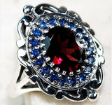 """Secrets of His Promises"" Stunning four carat genuine Mozambique fire Garnet surrounded by lab blue sapphires set in solid ornate sterling silver."