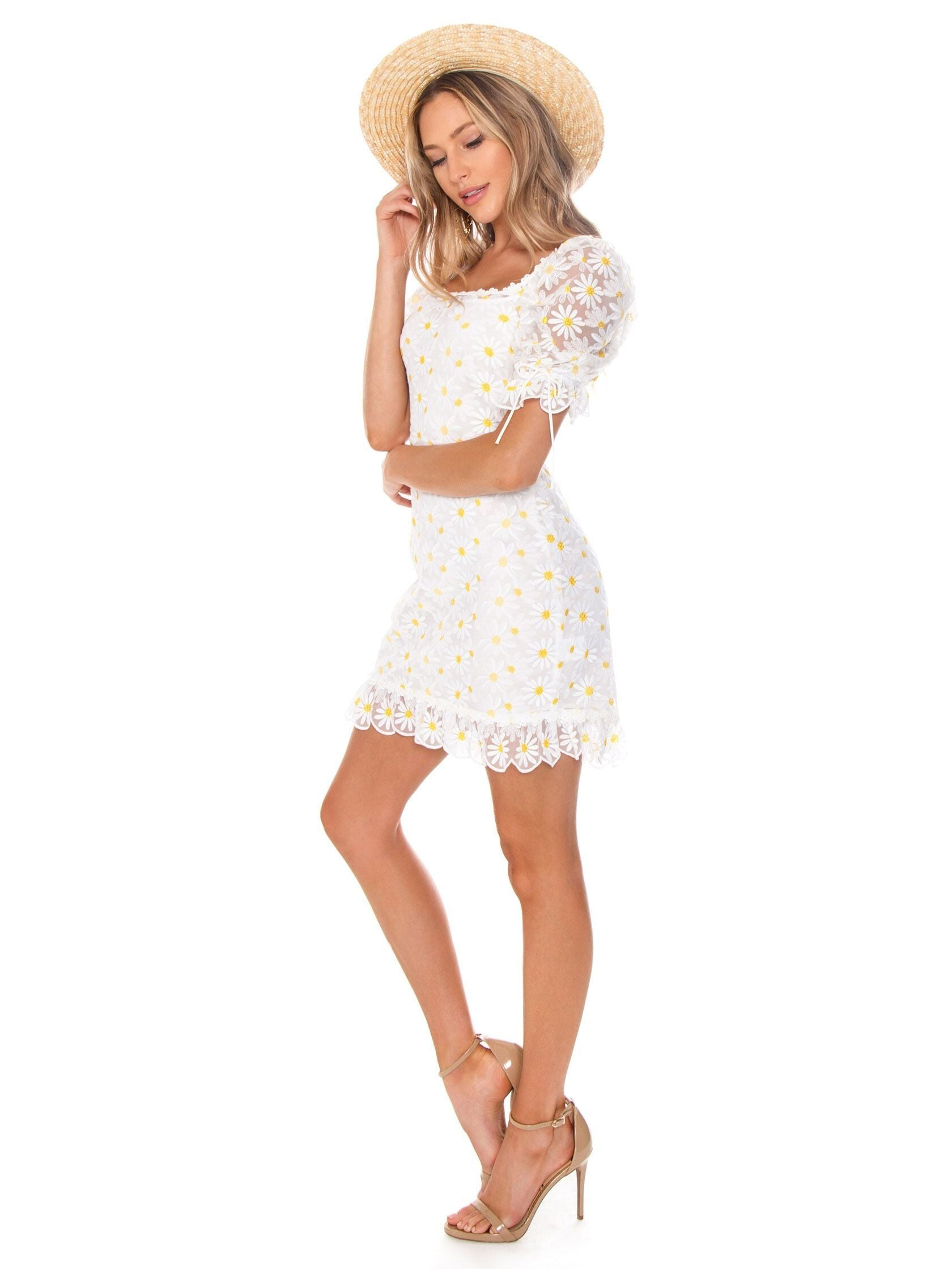 Woman wearing a dress rental from For Love & Lemons called Brulee Daisy Mini Dress
