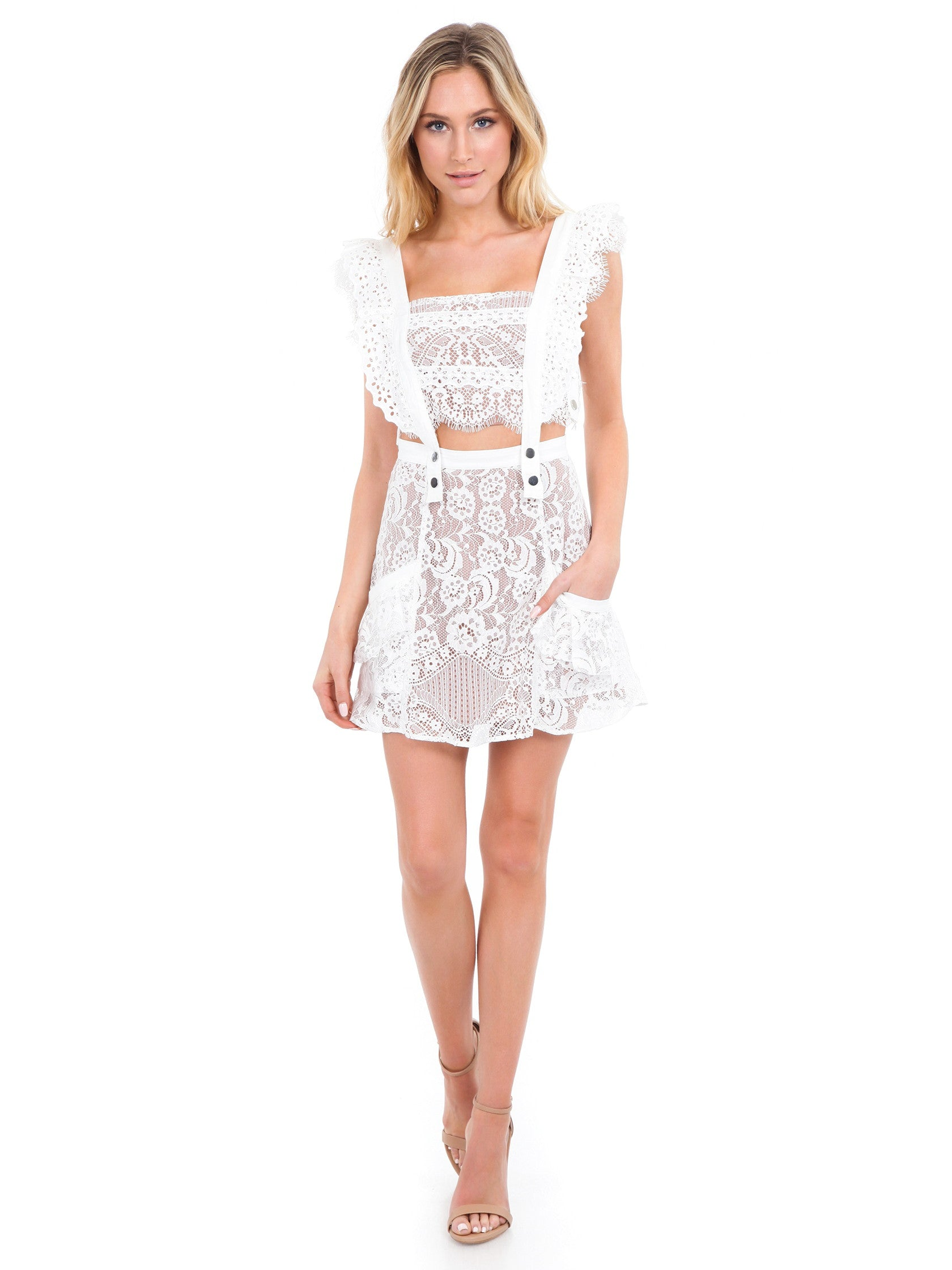Woman wearing a dress rental from For Love & Lemons called Tati Pinafore Lace Dress