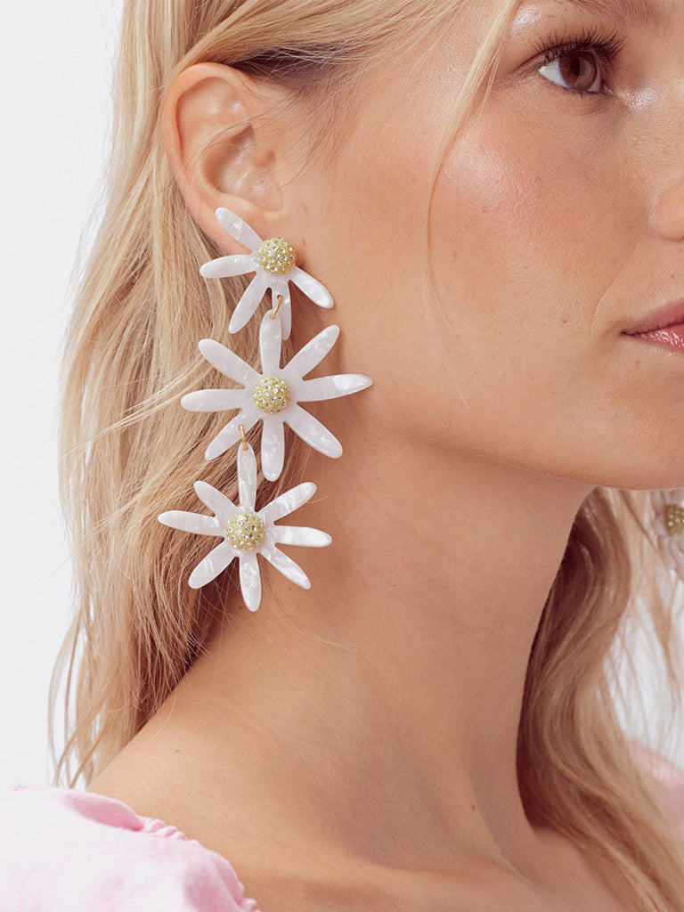 Women wearing a earrings rental from For Love & Lemons called Lucite Daisy Earrings