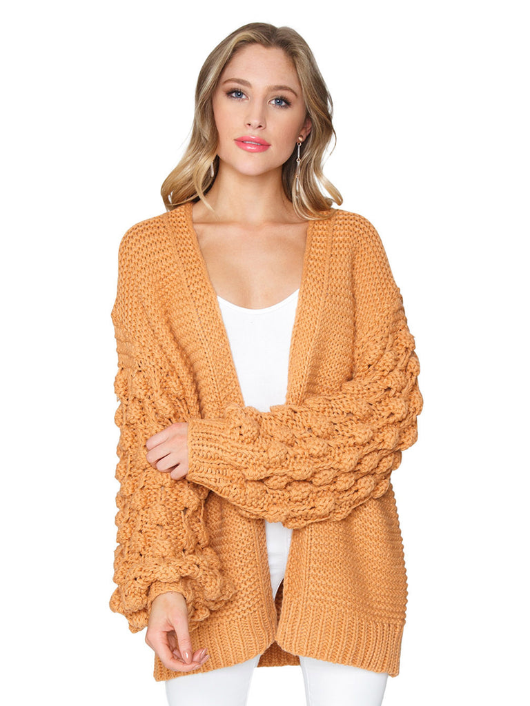 Women wearing a cardigan rental from FashionPass called Charlize Pom Pom Sleeve Cardigan