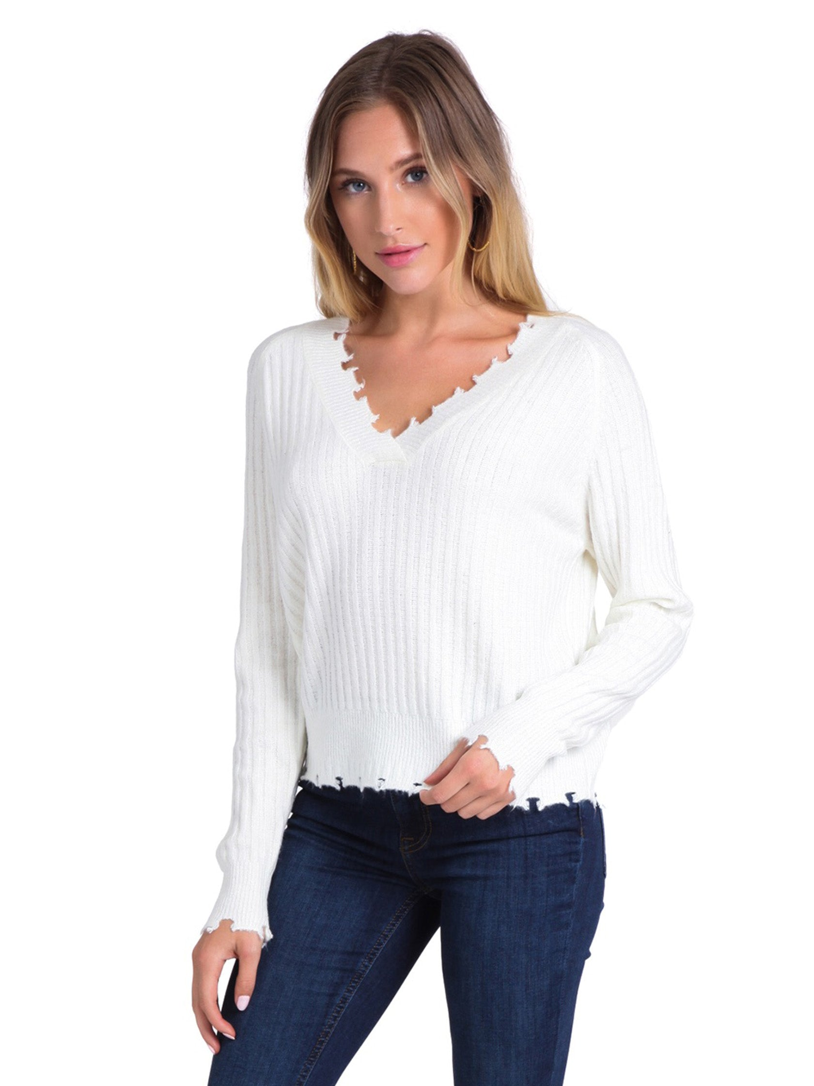Woman wearing a sweater rental from FashionPass called Distressed Ivory Sweater
