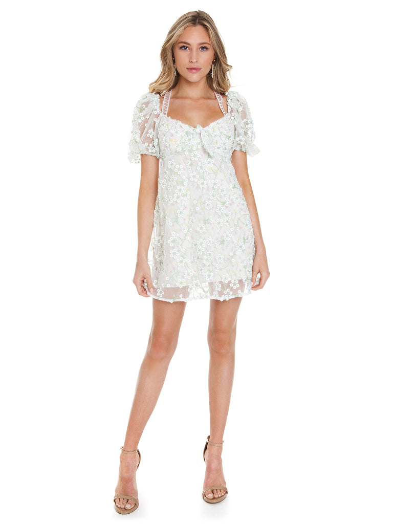Woman wearing a dress rental from For Love & Lemons called Peony Smocked Top