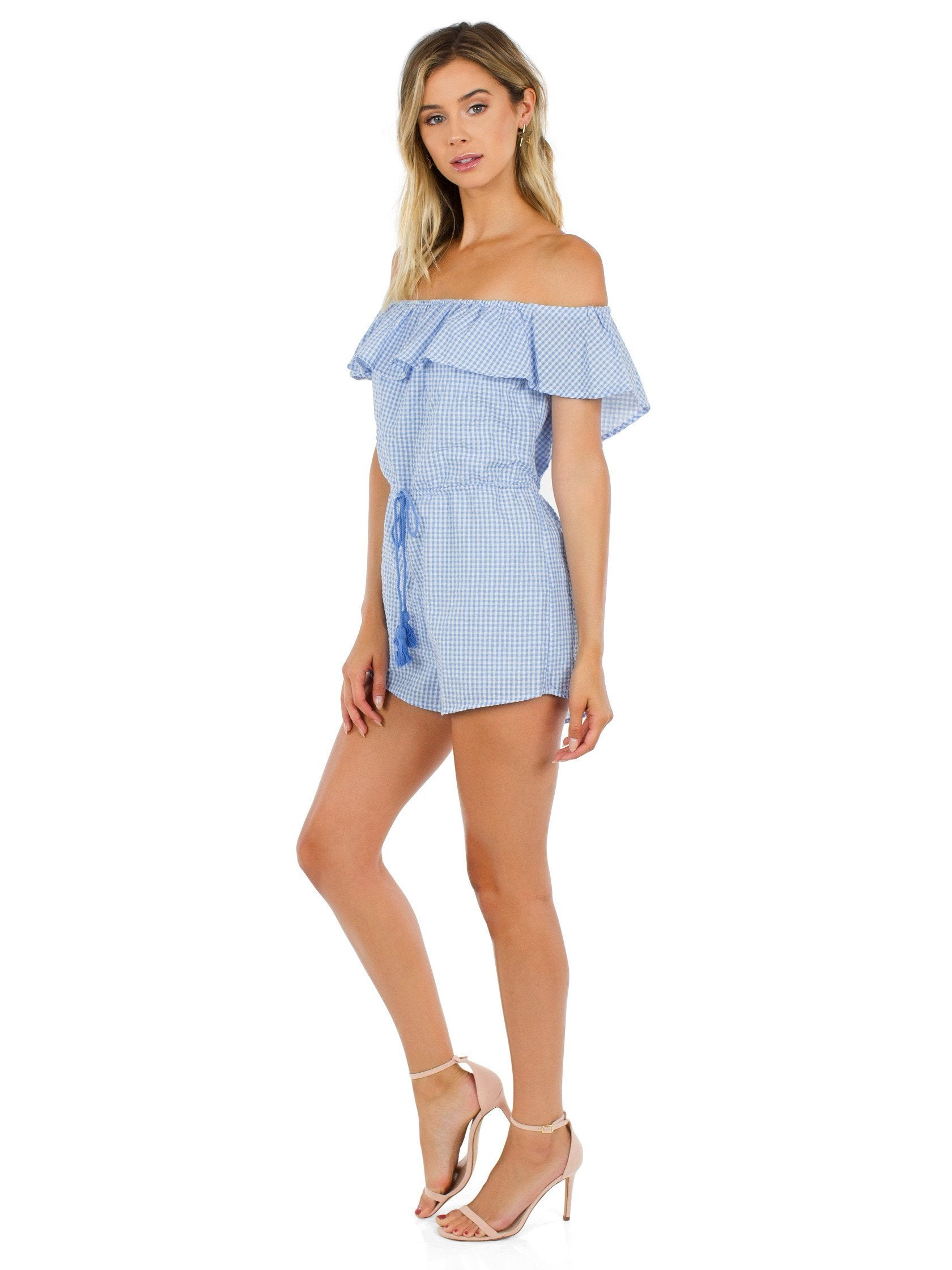 Woman wearing a romper rental from FashionPass called Going Gingham Romper