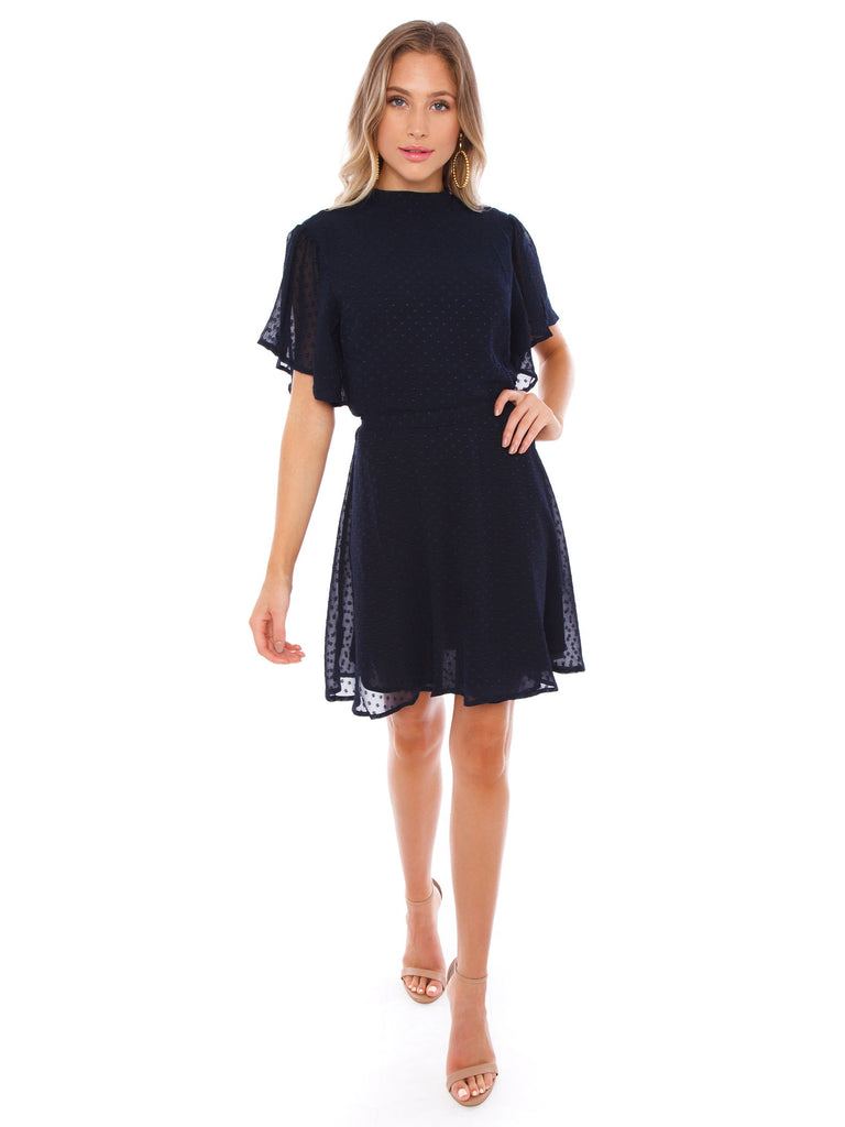 Women wearing a dress rental from Bishop + Young called Velvet Flutter Sleeve Wrap Dress
