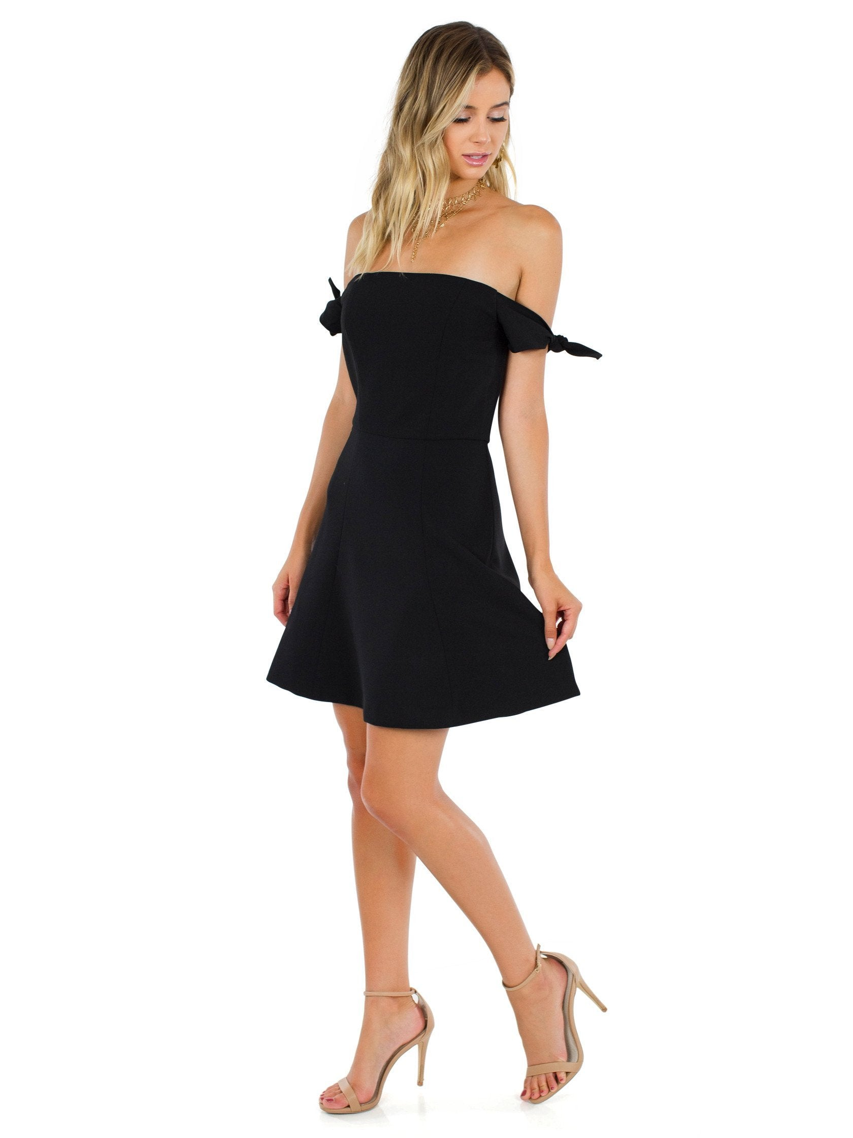 Woman wearing a dress rental from French Connection called Whisper Light Off The Shoulder Dress