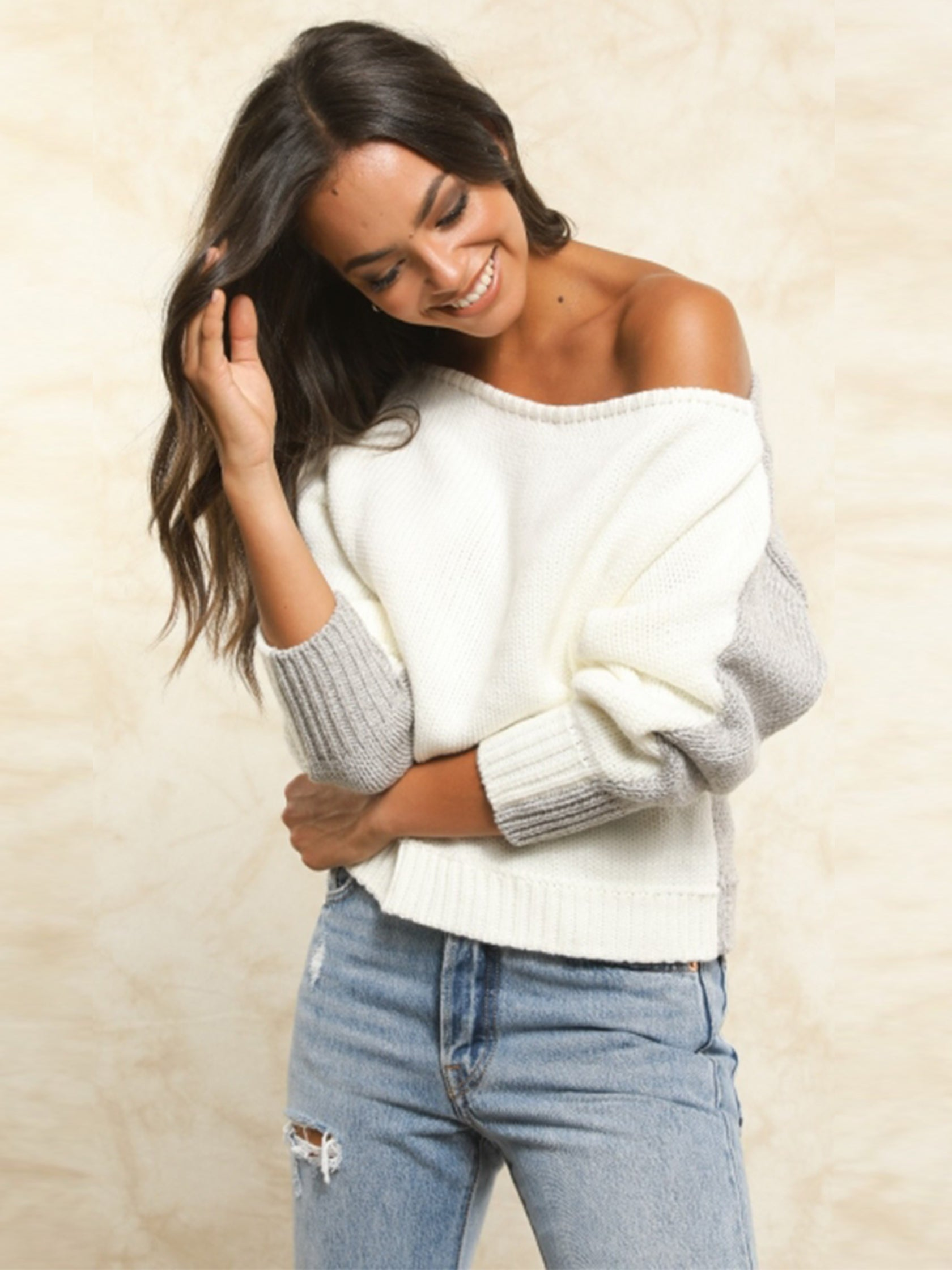 Woman wearing a sweater rental from FLETCH called Hannah Off Shoulder Reversible Sweater