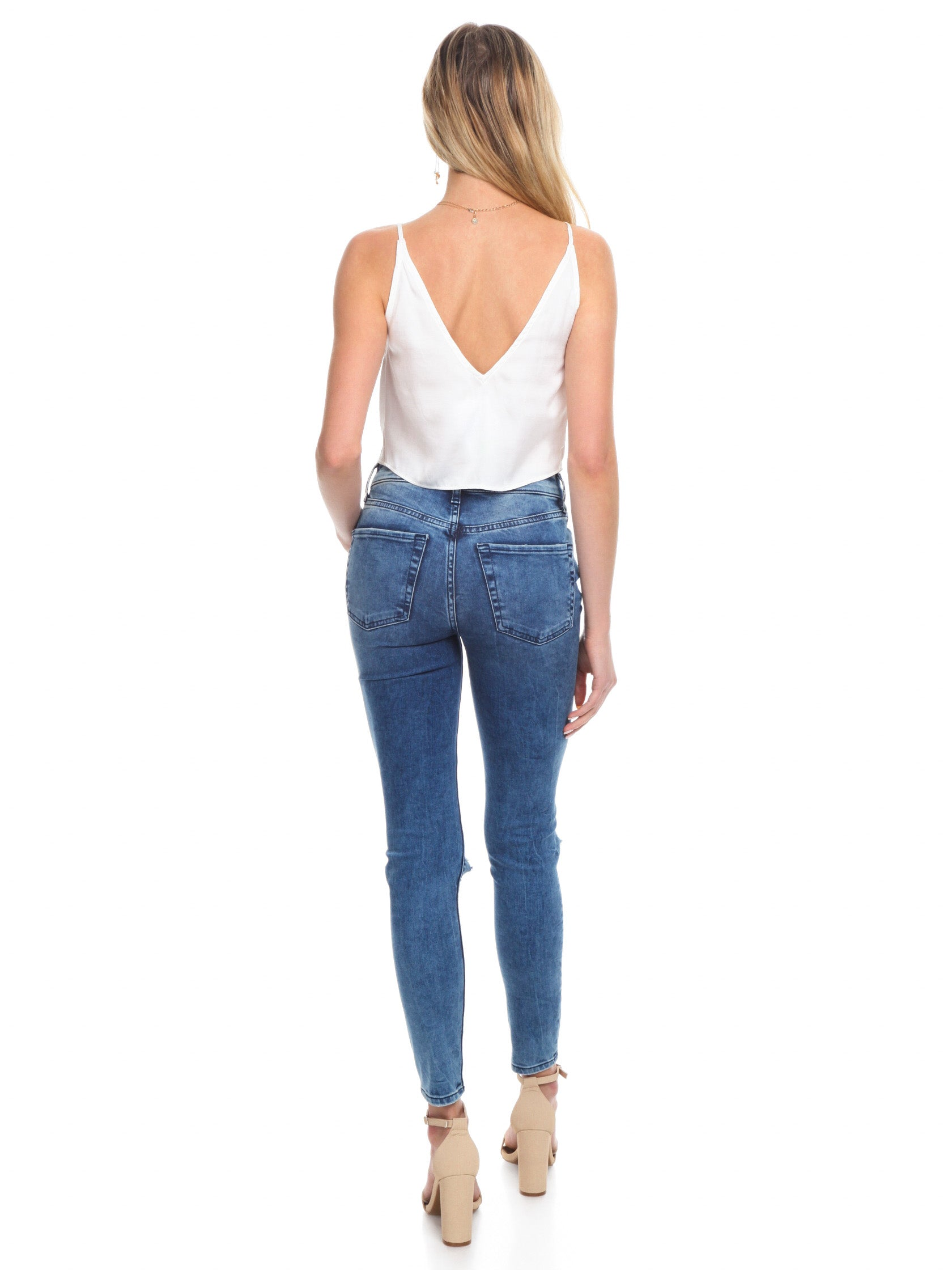 Women wearing a denim rental from Free People called High Rise Busted Skinny Jeans