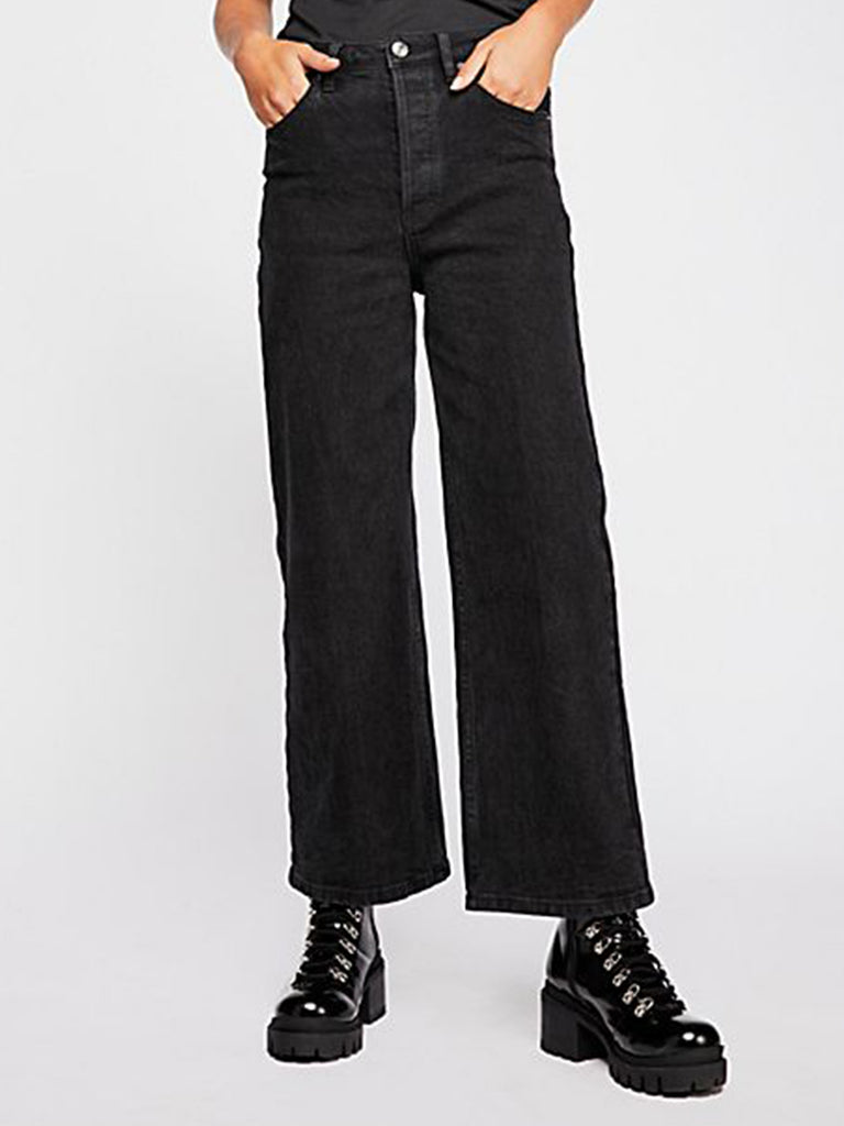 Woman wearing a denim rental from Free People called Campbell High Slit Pants