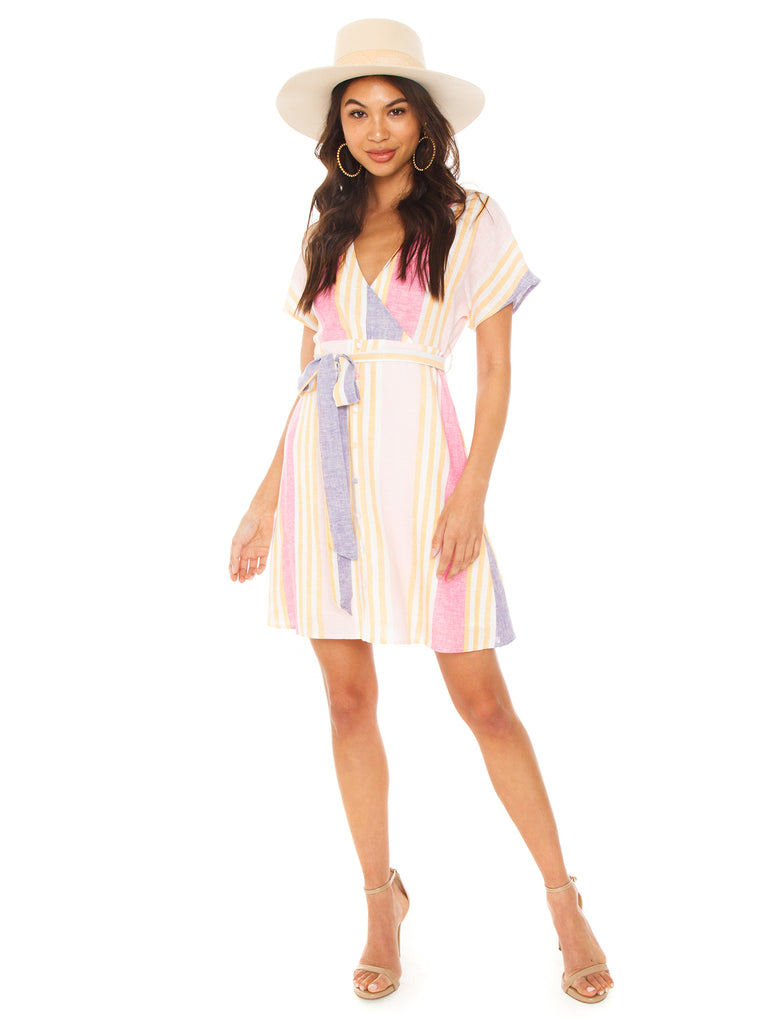 Girl wearing a dress rental from Line & Dot called Elsie Ruffle Wrap Dress