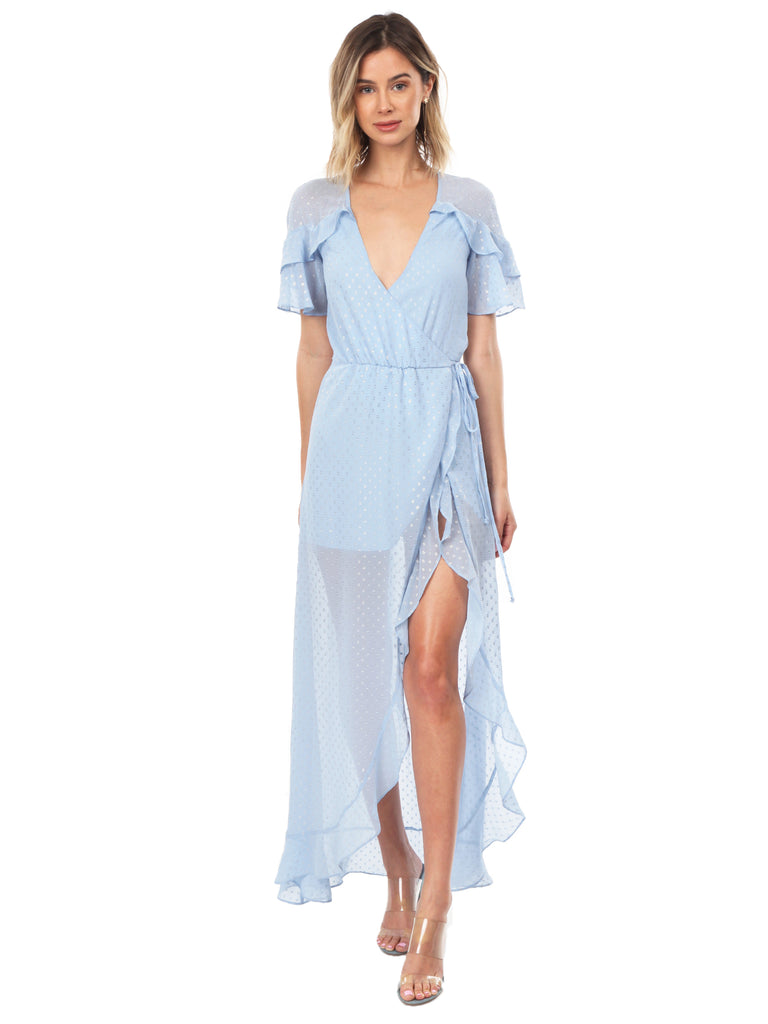 Woman wearing a dress rental from For Love & Lemons called Meryl Long Sleeve Wrap Maxi Dress