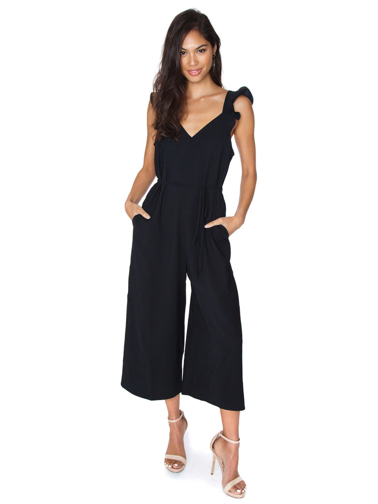 Woman wearing a jumpsuit rental from Line & Dot called Juniper Cable Knit Sweater