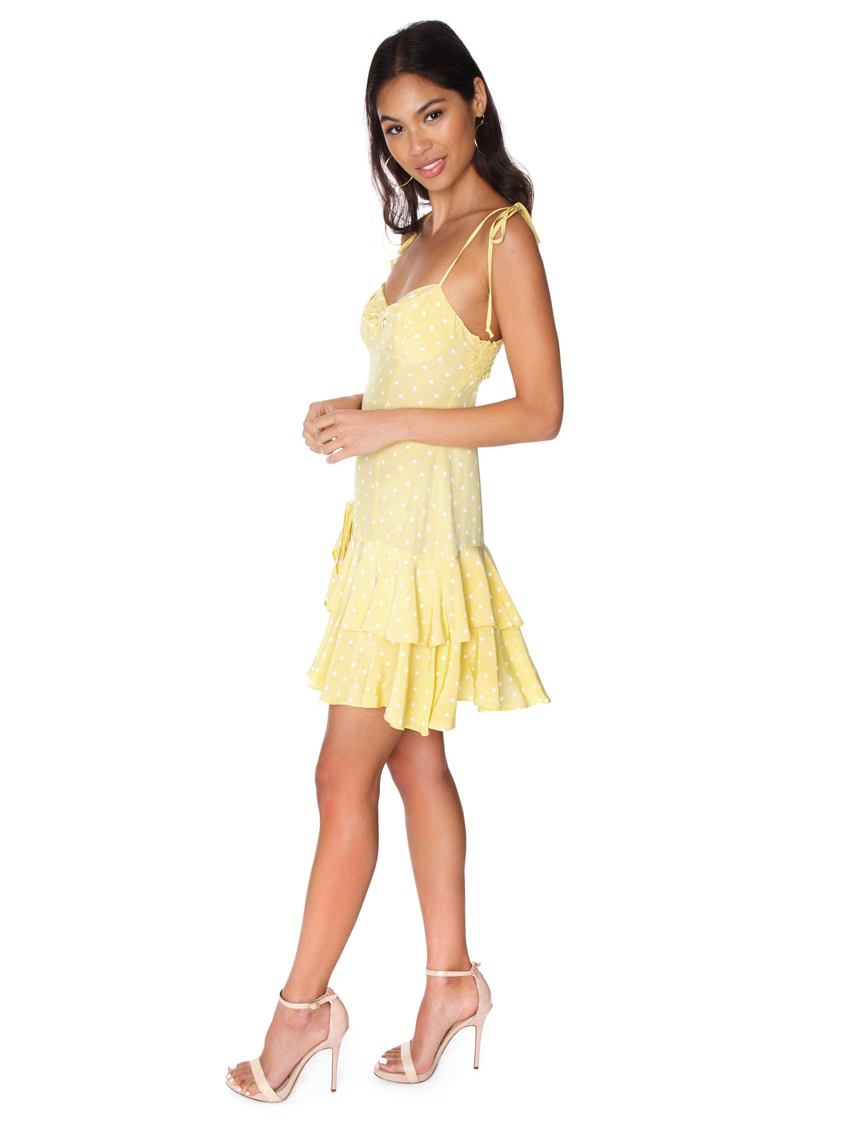 Woman wearing a dress rental from For Love & Lemons called Limoncello Tiered Ruffle Dress