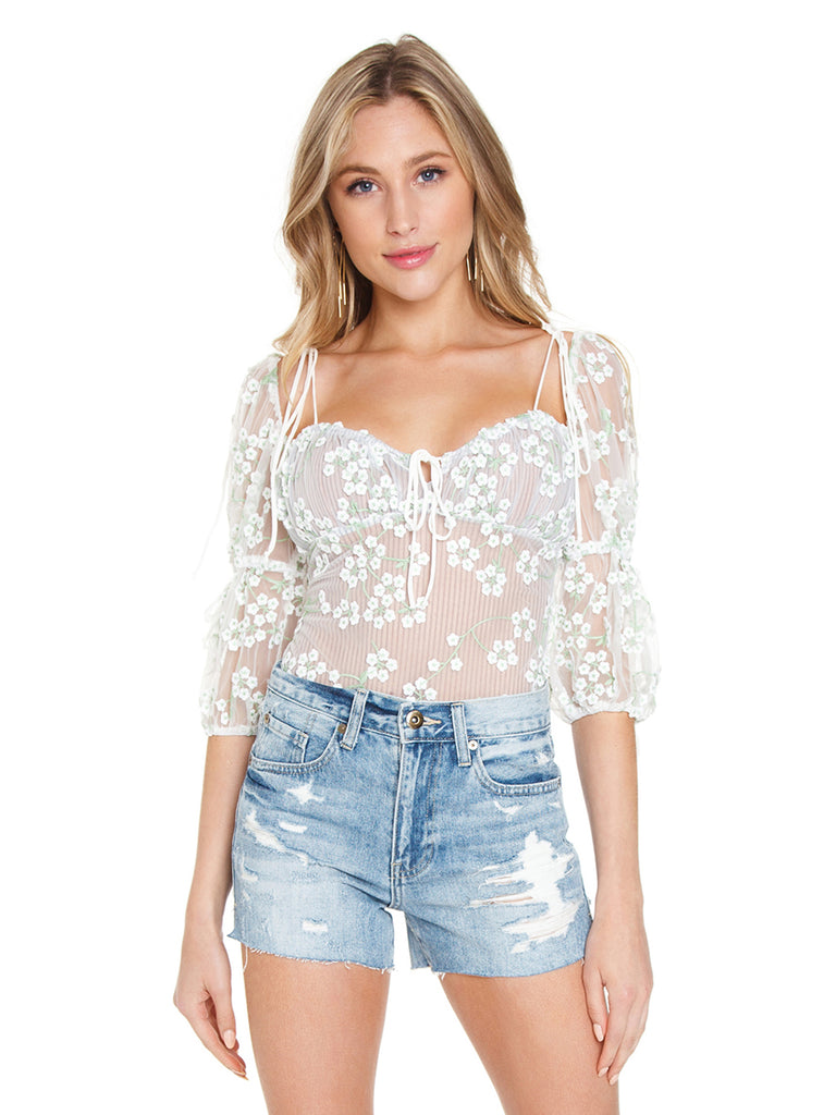 Girl wearing a bodysuit rental from For Love & Lemons called Peony Smocked Top