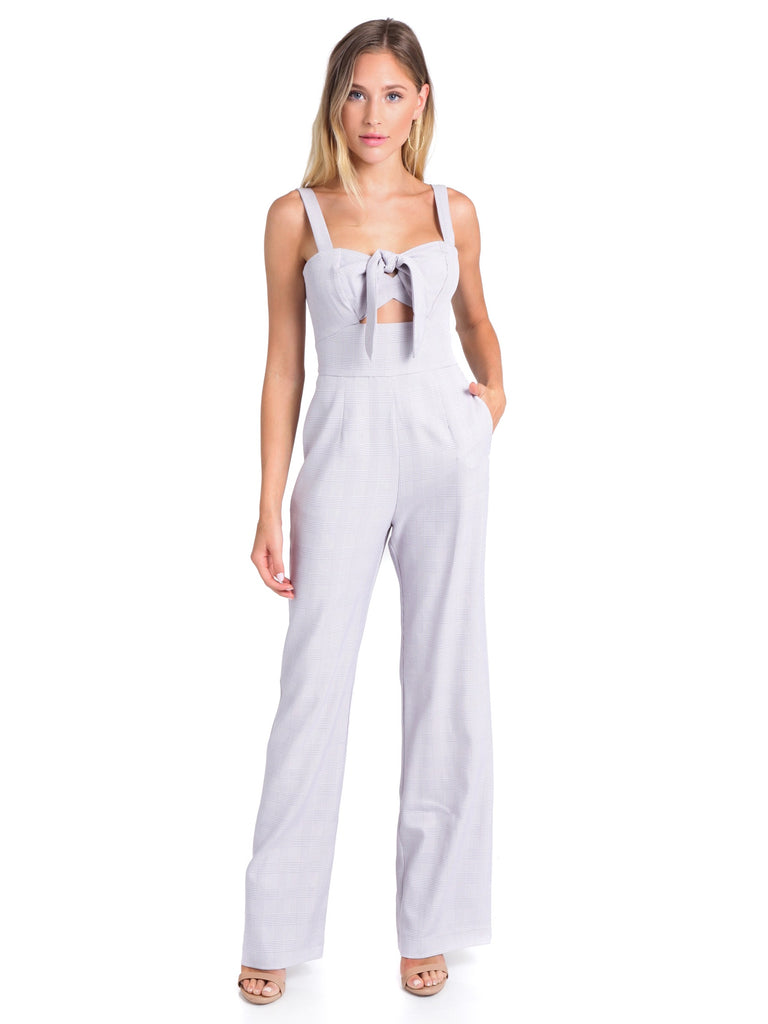 Woman wearing a jumpsuit rental from WAYF called Eyelet Apron Jumpsuit