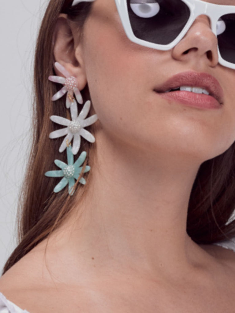 Woman wearing a earrings rental from For Love & Lemons called Peony Smocked Top