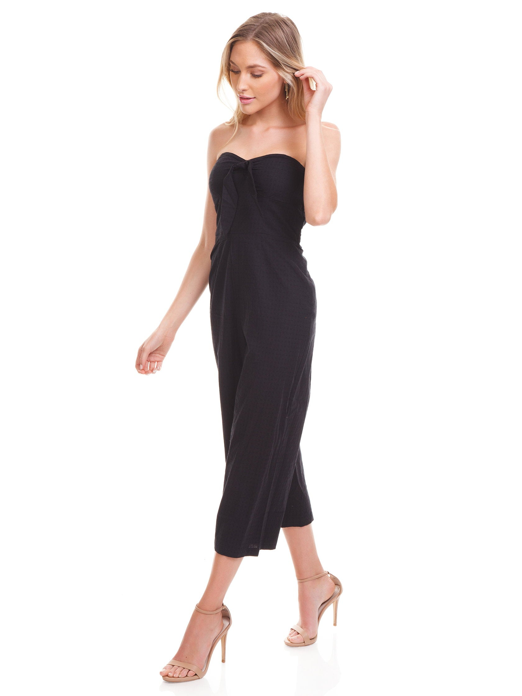 Woman wearing a jumpsuit rental from MINKPINK called Say It Right Strapless Jumpsuit