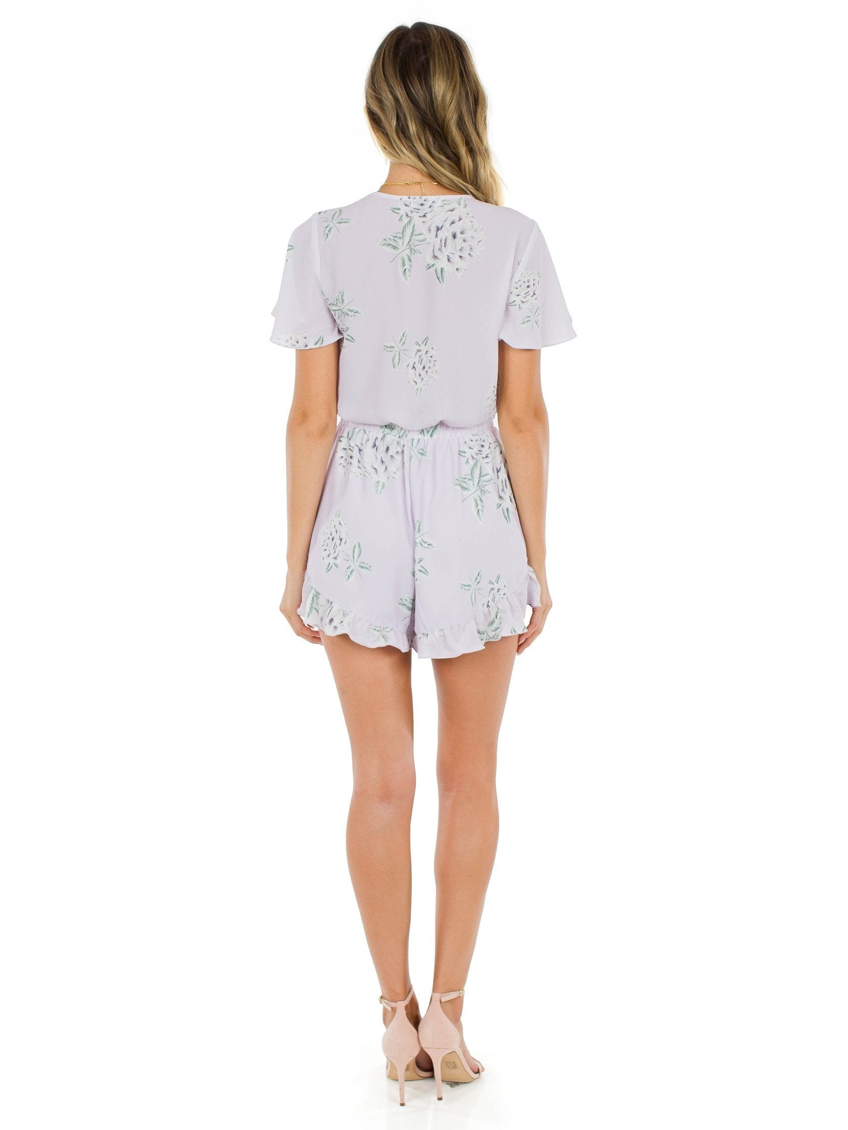 Girl wearing a romper rental from Show Me Your Mumu called Riviera Romper