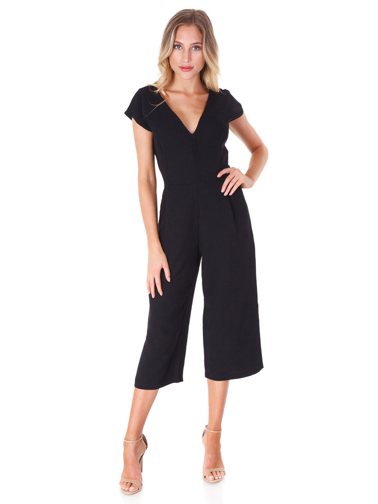 Woman wearing a jumpsuit rental from Bishop + Young called Flutter Sleeve Wide Leg Jumpsuit