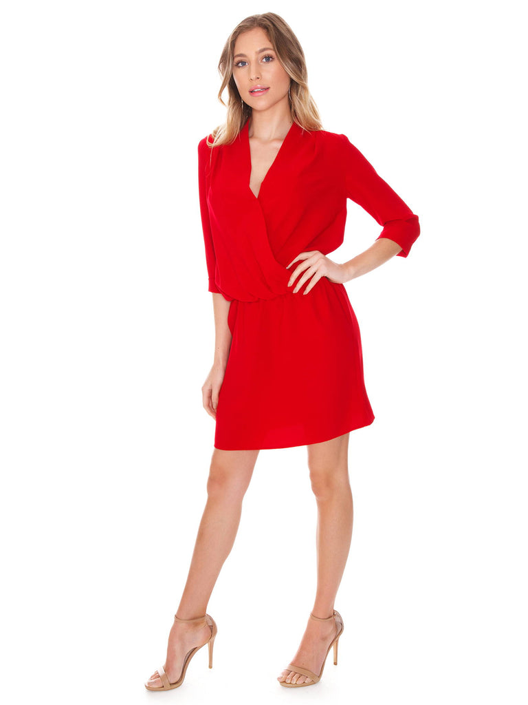 Woman wearing a dress rental from Amanda Uprichard called Velvet Flutter Sleeve Wrap Dress