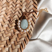 Beck Jewels Aquamarine stone adorned with white pearls pendant hanging from a gold filled necklace