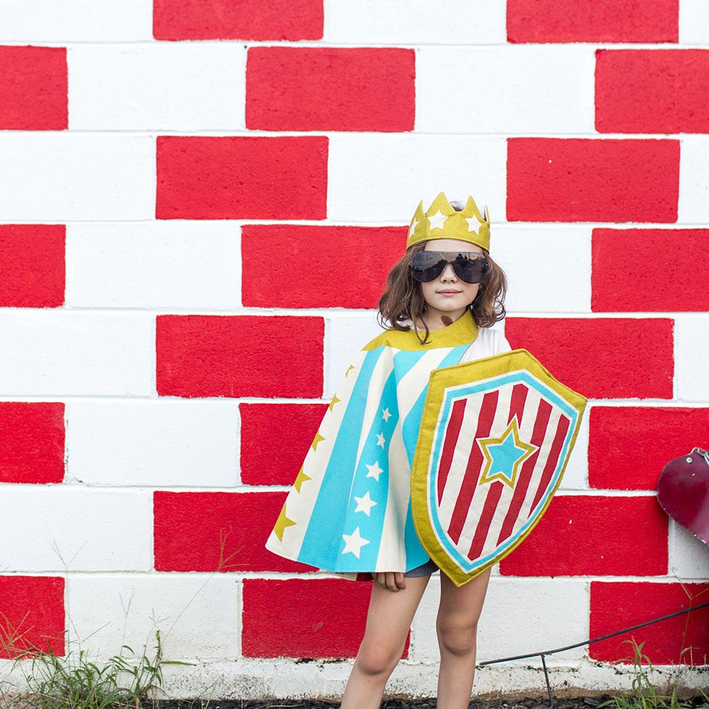 Child Superhero Costume in Action Blue Stripe Cape against wall