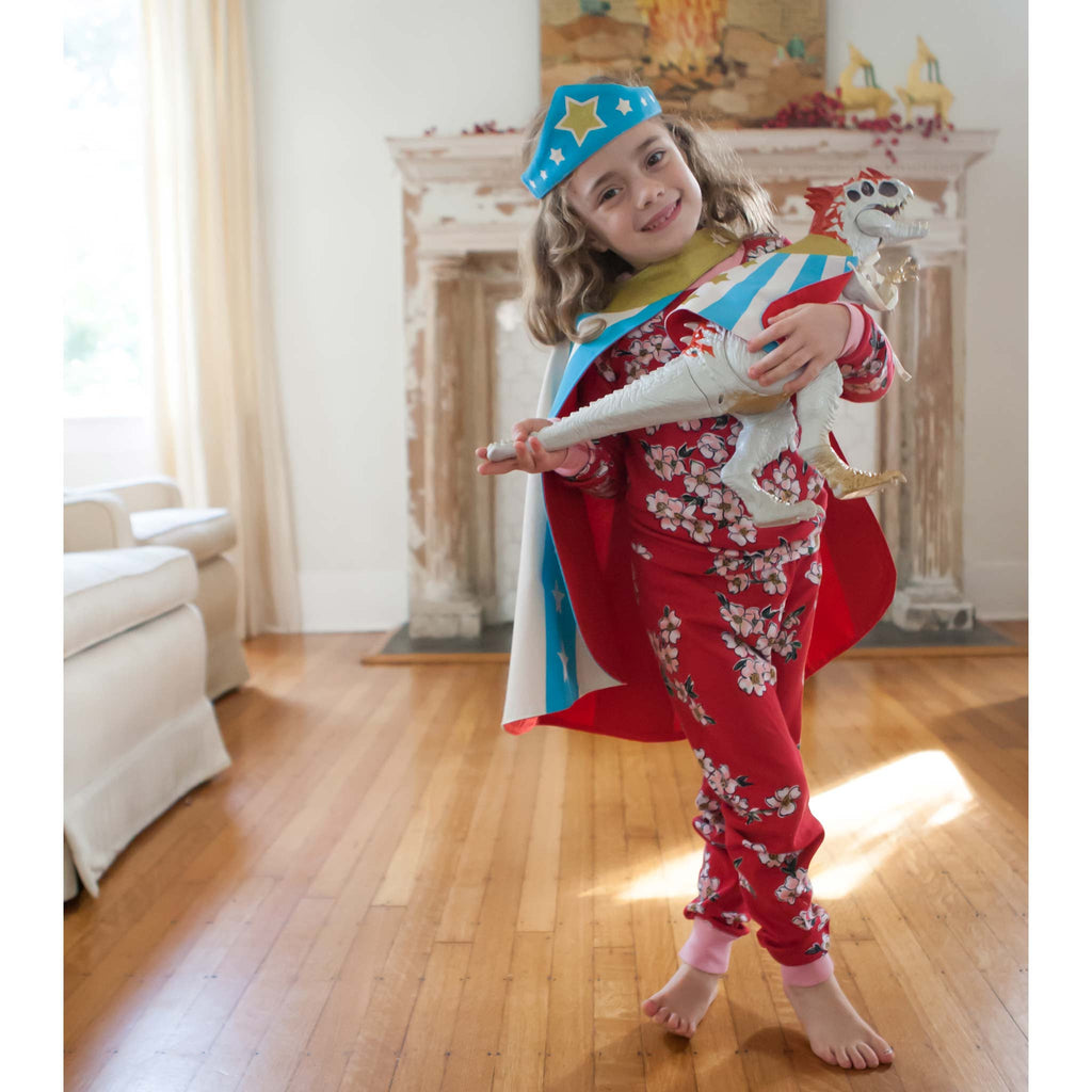 child wearing pajamas superhero costume holding toy