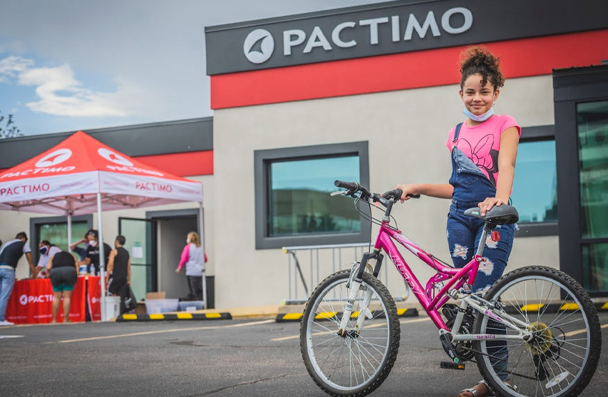 A young girl with her new bike at the Pactimo office