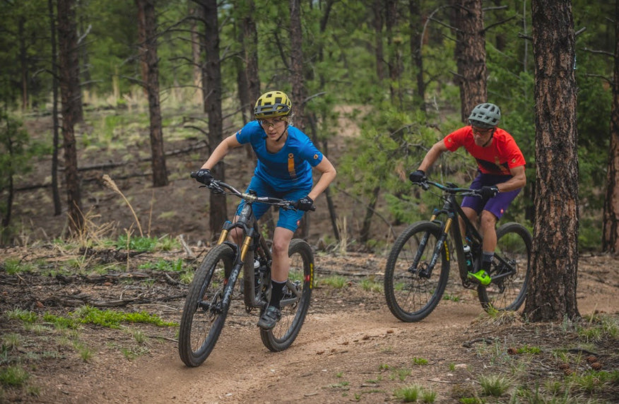 Male and female mountain bikers riding singletrack through the trees