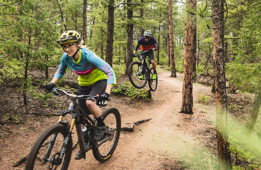 Male and female cyclists ripping through the trees