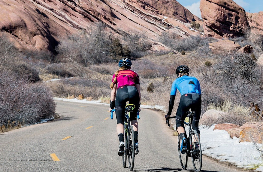 Male and female cyclists riding through Red Rocks Park, both wearing Storm+ Jerseys