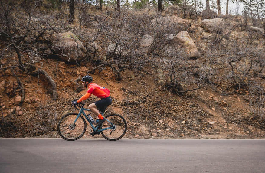 Cyclist on mountainous road wearing a bright colored Summit Aero Mesh Jersey