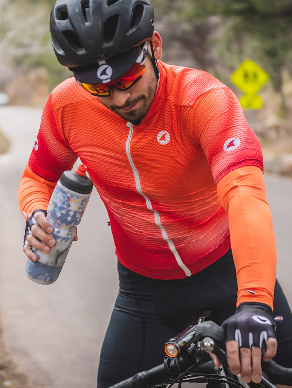 Cyclist stopping to take a drink from a water bottle, wearing the Summit Aero Mesh Jersey and matching Summer Sleeves