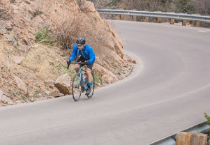 Male cyclist riding downhill waering a Divide Wind Jacket